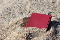 Livre rouge sur le sable sur un fond trouble, couvert de sable, enterré dans le sable Images libres de droits