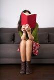 Livre rouge sur le visage se reposant de femme Photographie stock libre de droits