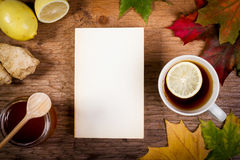 Livre, thé et miel sur la table avec des feuilles d'automne Image stock