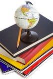Livres d'école et un globe miniature Photographie stock libre de droits