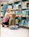 Livres d'And Boy Selecting de professeur féminin dans la bibliothèque photos libres de droits