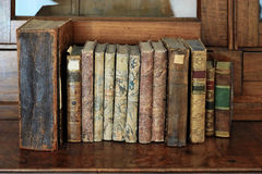 Livres dans une rangée sur des étagères à livres Photos stock