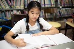 Livres de lecture asiatiques d'étudiants dans la bibliothèque image libre de droits