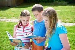 Livres de lecture d'enfants d'amis dehors Photo stock