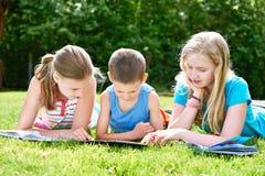 Livres de lecture d'enfants d'amis dehors sur l'herbe Images libres de droits