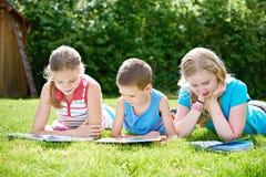 Livres de lecture d'enfants d'amis dehors sur l'herbe Photo stock