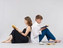 Livres de lecture d'homme et de femme ensemble Photo stock