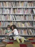 Livres de lecture de garçon et de fille dans la bibliothèque Photos stock