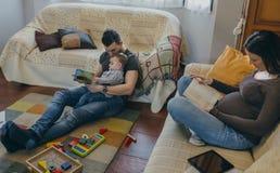 Livres de lecture de famille dans le salon photos libres de droits