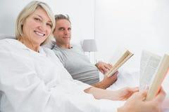 Livres de lecture heureux de couples dans le lit Image libre de droits