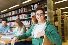 Livres de lecture heureux de garçon d'étudiant dans la bibliothèque Image libre de droits
