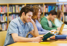 Livres de lecture heureux de garçon d'étudiant dans la bibliothèque Photographie stock libre de droits