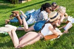 Livres de lecture multi-ethniques d'étudiants tout en se trouvant sur l'herbe et étudiant en parc Images libres de droits