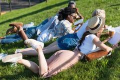 Livres de lecture multi-ethniques d'étudiants tout en se trouvant sur l'herbe et étudiant en parc Photographie stock