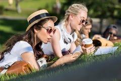 Livres de lecture multi-ethniques de filles tout en se trouvant sur l'herbe et étudiant en parc Photographie stock libre de droits