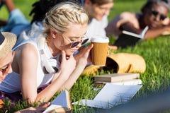 Livres de lecture multi-ethniques de filles tout en se trouvant sur l'herbe et étudiant en parc Photos libres de droits