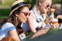 Livres de lecture multi-ethniques de filles tout en se trouvant sur l'herbe et étudiant en parc Photos stock