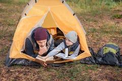 livres de lecture de père et de fils tout en se situant dans la tente images libres de droits