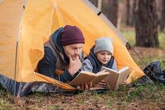 livres de lecture de père et de fils tout en se trouvant ensemble photographie stock libre de droits