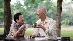 Livres de lecture supérieurs asiatiques de couples, apprenant l'investissement et la boisson Photos libres de droits