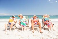Livres de lecture supérieurs d'amis sur des chaises de plage Photos stock