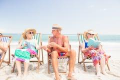 Livres de lecture supérieurs d'amis sur des chaises de plage Photo stock