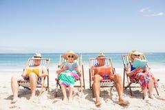 Livres de lecture supérieurs d'amis sur la chaise de plage Image libre de droits