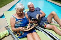 Livres de lecture supérieurs de couples sur la chaise longue Images stock