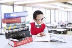 Livres de littérature d'étude de garçon à la bibliothèque Photographie stock