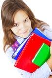 Livres de sourire de fixation de fille d'isolement au-dessus du blanc Image stock
