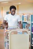 Livres de With Trolley Of de bibliothécaire dans la bibliothèque Images stock