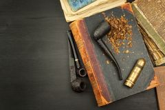 Livres de tuyau et d'antiquité de tabagisme Tuyau de tabac sur les livres antiques Détendez en lisant de vieux livres tabagisme Images libres de droits