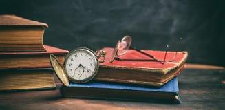 Livres de vintage et montre de poche sur le fond foncé photo libre de droits