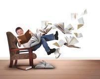 Livres de vol de lecture de garçon dans la chaise sur le blanc Photographie stock libre de droits