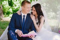 Livres dehors de sourire de caresse et de lecture de jeunes mariés, décor, pivoines, fleurs, mode de vie, mariage, famille, amour Photographie stock