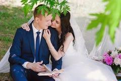Livres dehors de sourire de caresse et de lecture de jeunes mariés, décor, pivoines, fleurs, mode de vie, mariage, famille, amour Photos libres de droits
