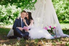 Livres dehors de sourire de caresse et de lecture de jeunes mariés, décor, pivoines, fleurs, mode de vie, mariage, famille, amour Images stock