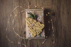 Livres enveloppés sur une table et des lumières de Noël Image libre de droits
