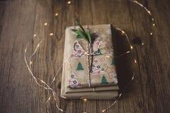 Livres enveloppés sur une table et des lumières de Noël Images libres de droits