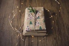 Livres enveloppés sur une table et des lumières de Noël Photos stock