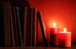 Livres et bougies de vintage sur le fond foncé photographie stock libre de droits