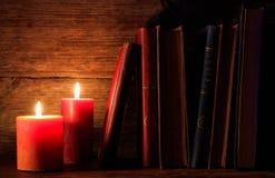 Livres et bougies de vintage sur le fond foncé image libre de droits