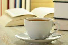 Livres et cuvette de café sur la table Photos libres de droits