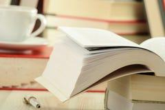 Livres et cuvette de café sur la table Images libres de droits