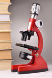 Livres et microscope rouge Images stock