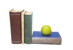 Livres et pomme verte d'isolement sur le fond blanc photos libres de droits