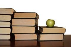 Livres et une pomme sur une table en bois photographie stock
