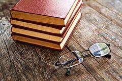 Livres et verres de lecture sur la table Images stock