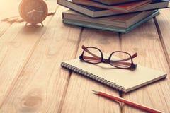 Livres et verres sur un bureau en bois de table Photo stock