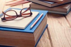 Livres et verres sur un bureau en bois de table Image libre de droits